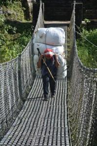 Ein Träger geht vollbeladen über eine Hängebrücke